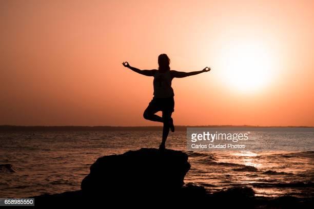 Woman practising yoga on rock in the Mediterranean Sea