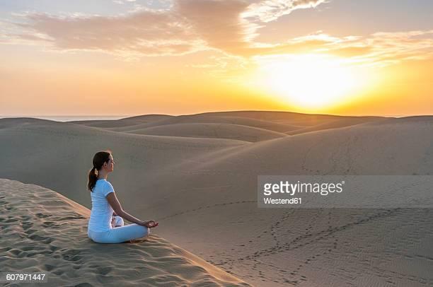 Woman practising yoga on sand dunes