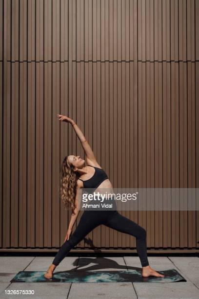 woman practising yoga - one mid adult woman only stock pictures, royalty-free photos & images
