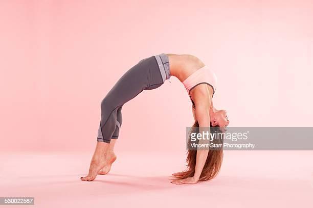 woman practising yoga - beugen oder biegen stock-fotos und bilder