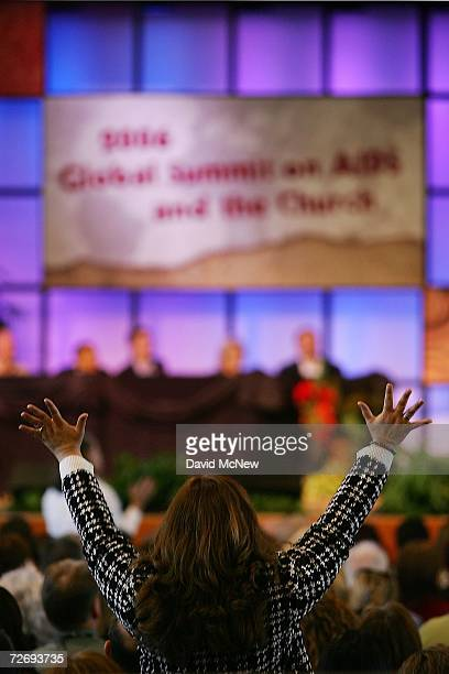 A woman praises God during the second annual Global Summit on AIDS and The Church at Saddleback Church where Sen Barack Obama Sen Sam Brownback and...