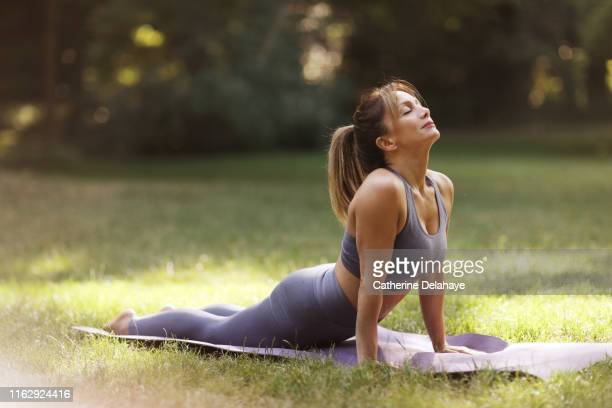 a woman praticing yoga in a park - instructor stock pictures, royalty-free photos & images