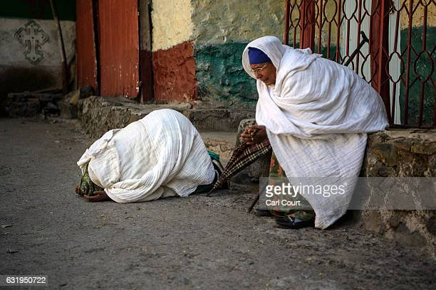 Woman pray in the grounds of a church as Timkat celebrations get under way on January 18 2017 in Gondar Ethiopia Timkat is the Ethiopian Orthodox...