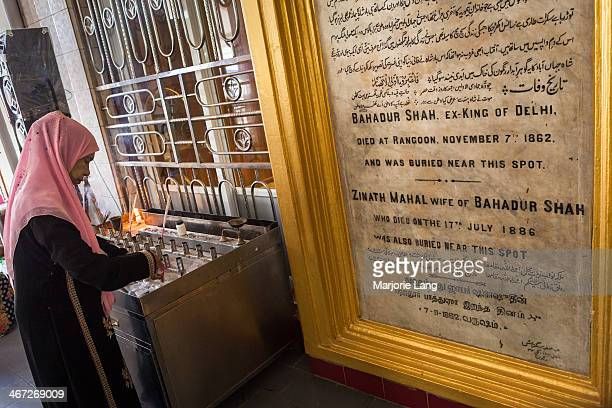 Woman praying and lighting candles at the mausoleum of Bahadur Shah Zafar, the last Mughal emperor. Yangon, Myanmar . Bahadur Shah Zafar was the last...