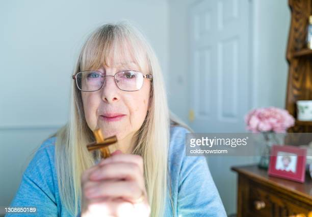 woman praying at home with wooden cross - symbolism stock pictures, royalty-free photos & images