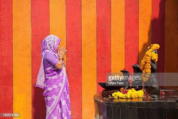 Woman praying at shrine.