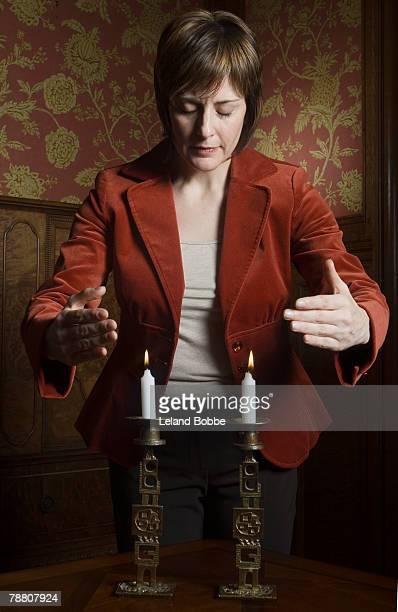 Woman Praying Before Shabbat Candles