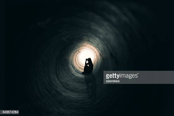 woman praying in a dark place - loneliness stock pictures, royalty-free photos & images