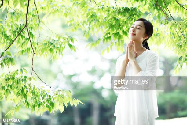 woman praying in a park