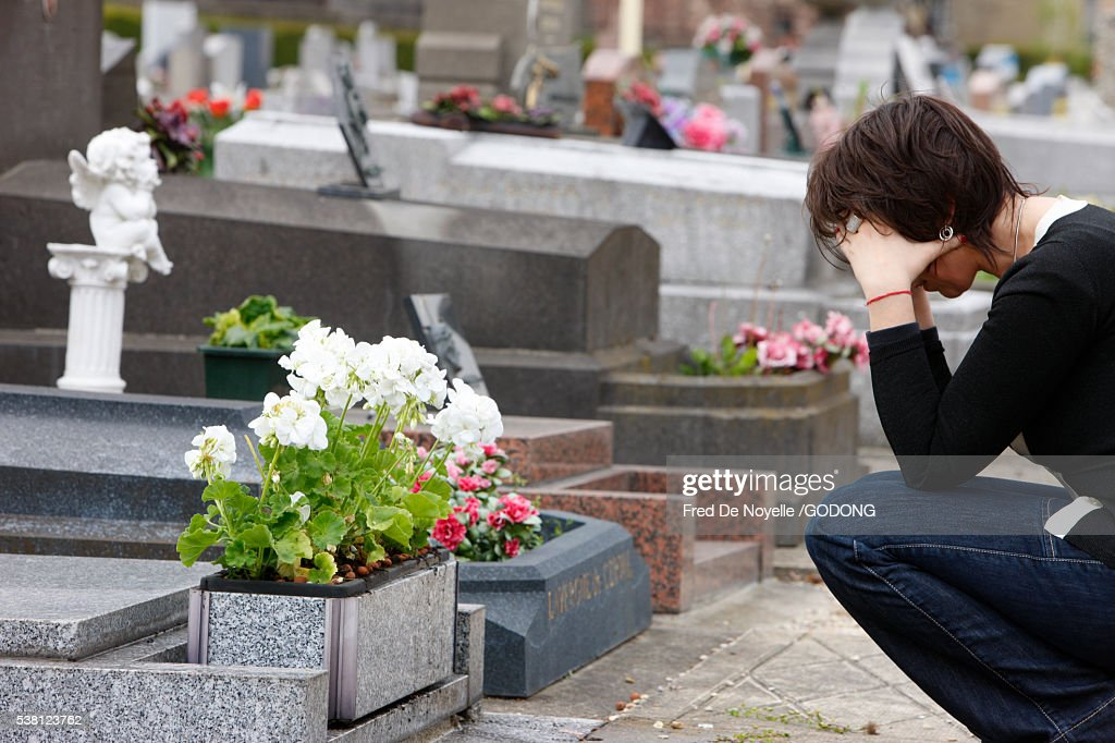 Woman praying in front of her mother's grave : Stock Photo