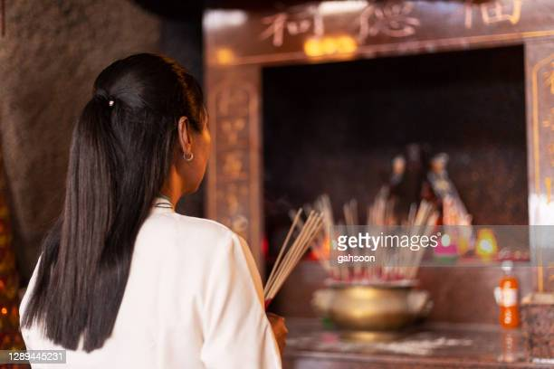woman praying in temple with incense sticks - religious vigil stock pictures, royalty-free photos & images