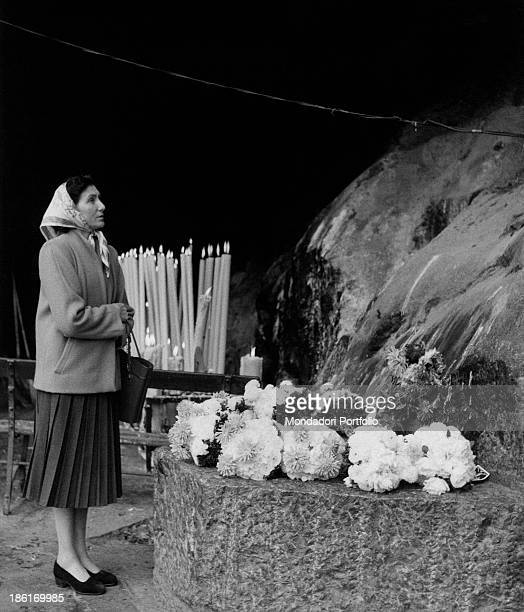A woman praying in the Grotto of Massabielle during the centenary of the apparitions of Our Lady to Saint Bernadette Soubirous Lourdes 22nd November...
