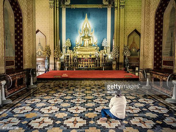 woman praying inside wat benchamabophit temple - wat benchamabophit stock photos and pictures