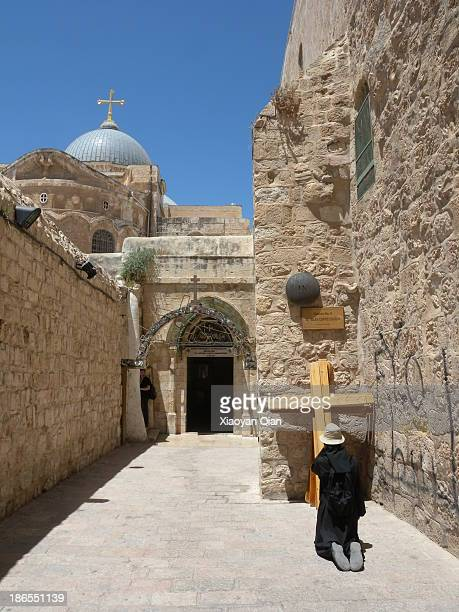 Woman praying on Station 9 in Via Dolorosa with the Holy Sepulchre in the background, Jerusalem.