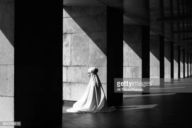woman, praying outfit, praying, istiqlal mosque complex, jakarta, indonesia. - masjid istiqlal stock pictures, royalty-free photos & images