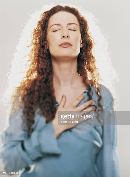 Woman Praying With Her Eyes Closed, One Hand on Her Chest