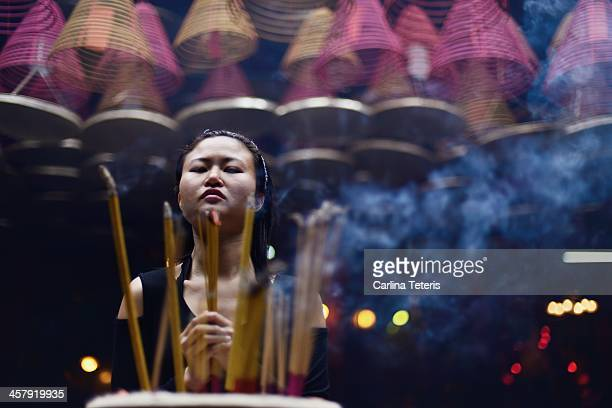 woman praying with incense - incense coils stock pictures, royalty-free photos & images