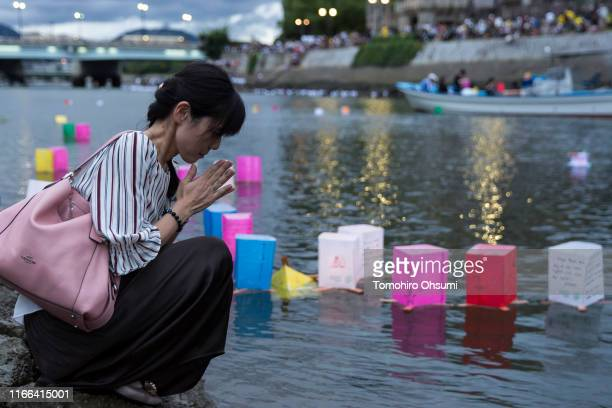A woman prays after placing a candle lit paper lantern on the river during an event to commemorate the 74th anniversary of the atomic bombing of...