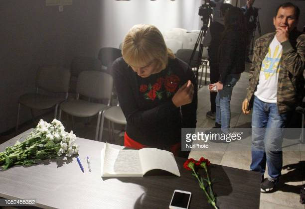 A woman prays after she writed a note to on a remembrance book in tribute of the victims of a college attack in the Crimean port city of Kerch in the...
