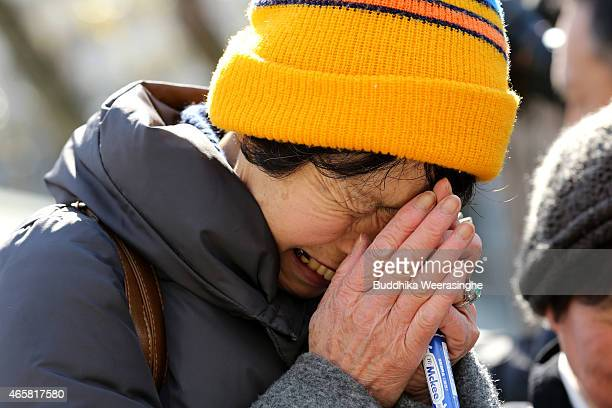 A woman prays as cries over the lighted bamboo candles placed in the shape of the date 311 to commemorate the victims of Great East Japan Earthquake...