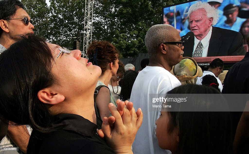 A woman prays as Rev. Blly Graham preaches at the Greater New York Billy Graham Crusade June 26, 2005 held in Flushing Meadows Corona Park in the Queens borough of New York. The three day crusade ending today will most likely be Graham's last mass event in the United States.