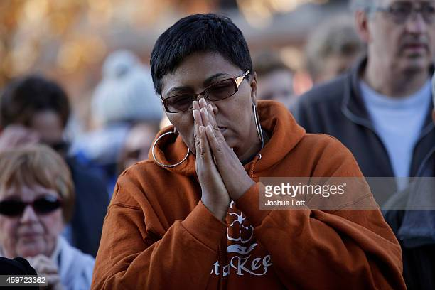 A woman prays as she joins demonstrators protesting the shooting death of Michael Brown outside the Buzz Westfall Justice Center November 29 2014 in...