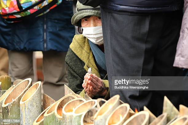A woman prays as she lights bamboo candles placed in the shape of the date 311 to commemorate the victims of Great East Japan Earthquake and Tsunami...