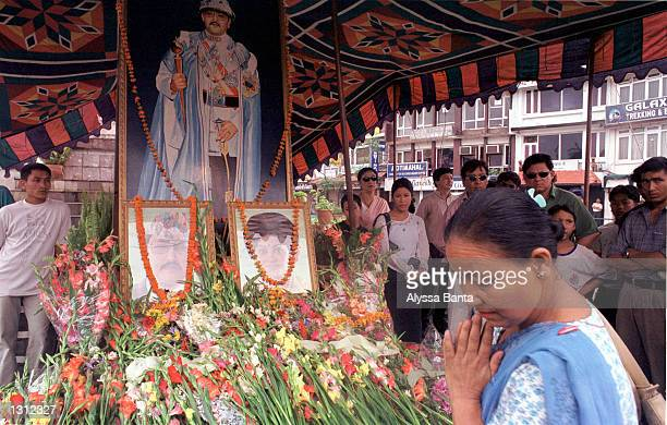 A woman prays as she passes flowers offered at a shrine with a portrait of Nepalese King Birendra and a photograph of the King and Queen Aishworya...