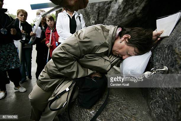 A woman prays as she touchs the stone beside the Statue of Our Lady of Lourdes at the entrance to the Grotto of Massabielle on September 12 2008 in...