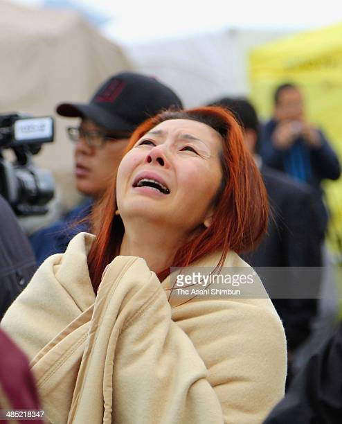 A woman prays as she waits for missing passengers of a sunken ferry at Jindo port on April 17 2014 in JindoGun South Korea At least six people are...