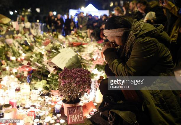 Woman prays at a makeshift memorial in front of the Bataclan theatre, one of the site of the attacks in Paris, on November 15 in Paris. Islamic State...
