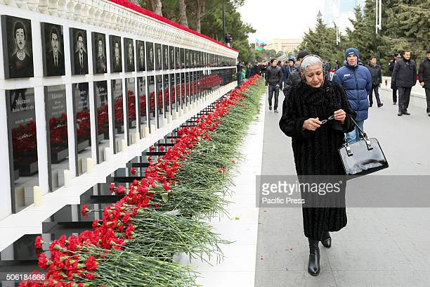 A woman prays at the Alley of Martyrs a cemetery and memorial dedicated to those killed by Soviet troops during the 1990 Black January crackdown in...