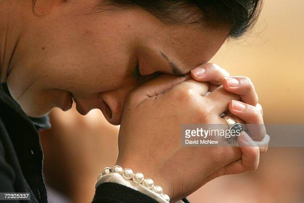 A woman prays at the Cathedral of Our Lady of the Angels where Monsignor Royale Vadakin urged 1100 Catholics gathered for midday Mass to reserve...