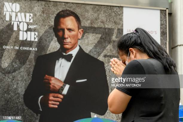 """Woman prays at the Erawan Shrine in front of an advertisement poster featuring Daniel Craig in the new James Bond movie """"No Time to Die"""" in Bangkok..."""