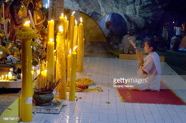 Woman prays at the foot of the big Buddha statue inside the Wat Tham Bo Ya cave. During Khao Phansa , anyone in Thailand can go to meditate in a...