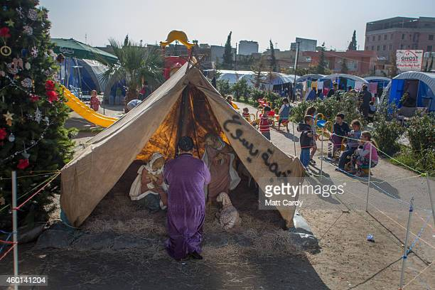 A woman prays at the Jesus Tent that has been erected in the grounds of Mar Elias Catholic Church in Ankawa which has become home to hundreds of...