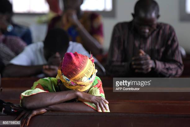 A woman prays at the Saint Paul Catholic Church in Freetown days after the partial collapse of a hillside that swept away hundreds of homes in a...