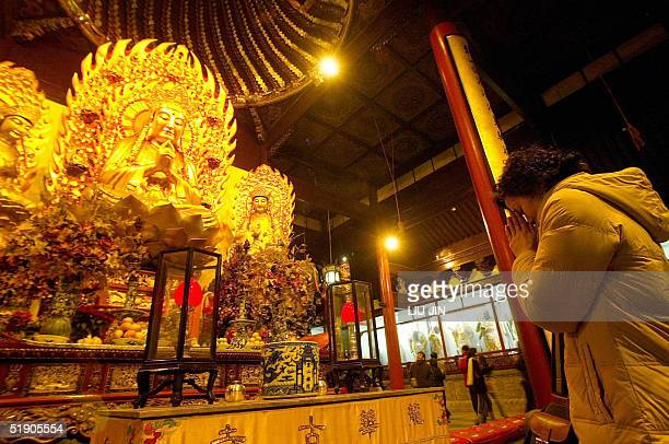 A woman prays before a Buddhist statue during New Year's celebrations at Longhua Temple in Shanghai 01 January 2005 For Chinese when the new year...