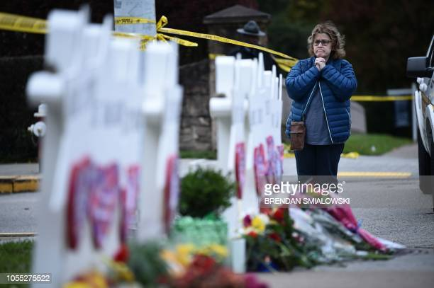 A woman prays before a memorial outside the Tree of Life synagogue after a shooting there left 11 people dead in the Squirrel Hill neighborhood of...