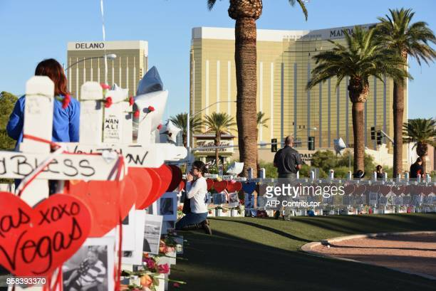 A woman prays beside 58 white crosses for the victims of Sunday night's mass shooting on Las Vegas Strip just south of the Mandalay Bay hotel October...