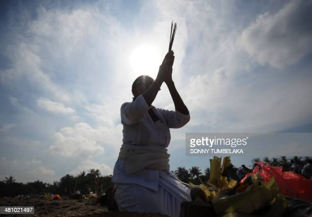 A woman prays during a Melasti ceremony prayer session at Petitenget beach in Kuta on Indonesia's resort island of Bali on March 28 2014 Melasti is a...