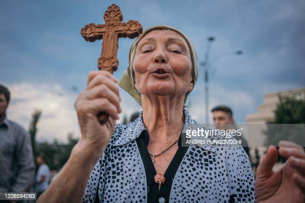 Woman prays during a protest against the Romanian government and its measures against the new coronavirus pandemic on July 12th in Bucharest, Romania.