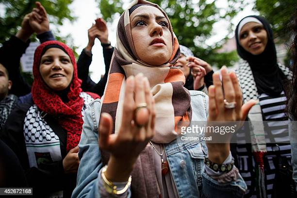 A woman prays during a rally for AlQuds Day an event intended to express solidarity with the Palestinian people on July 25 2014 in Berlin Germany...