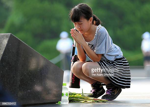 A woman prays for the abomb victims prior to the peace memorial ceremony on the 71st anniversary of the atomic bomb dropping at the Hiroshima Peace...