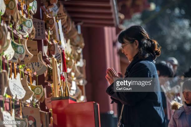 A woman prays for the new year at Tsurugaoka Hachimangu Shinto shrine on January 1 2018 in Kamakura Japan 'Hatsumode' is the first Shinto shrine...