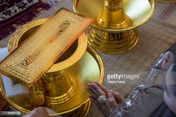 A woman prays in front of a golden sheet engraved with sacred Buddhist scriptures inside the main hall of a temple where a Kathina festival is...