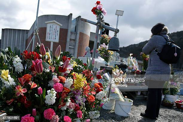 A woman prays in front of a monument on the third anniversary of the Great East Japan Earthquake and Tsunami at the Okawa elementary school destroyed...