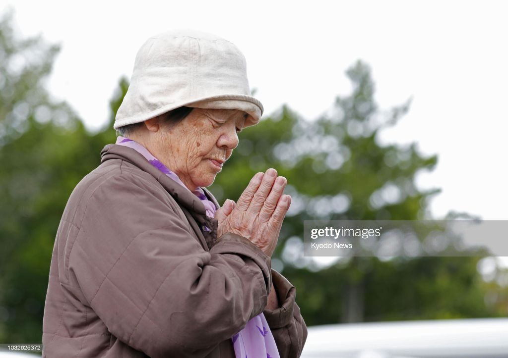 A woman prays in front of an evacuation center in Atsuma, Hokkaido, on Sept. 13, 2018, one week after a strong earthquake struck Japan's northernmost main island. ==Kyodo