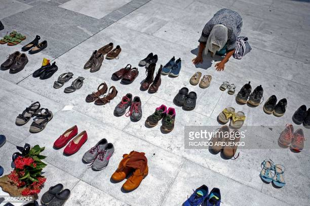 A woman prays in front of hundreds of shoes that were displayed in memory of those killed by Hurricane Maria in front of the Puerto Rican Capitol in...