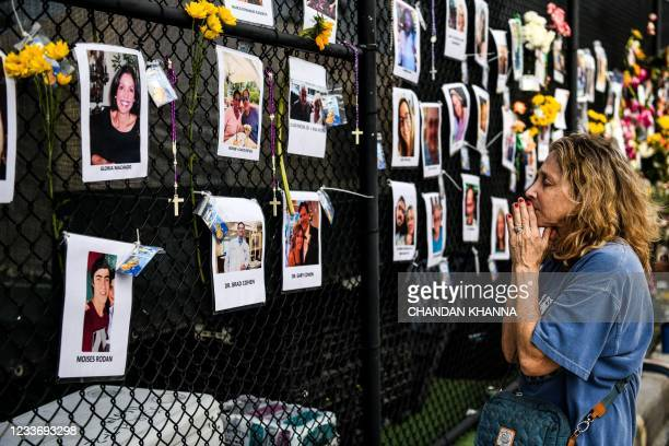 Woman prays in front of photos at the makeshift memorial for the victims of the building collapse, near the site of the accident in Surfside,...